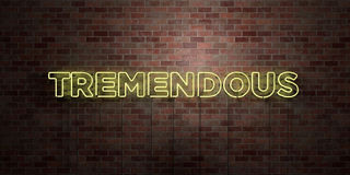 TREMENDOUS - fluorescent Neon tube Sign on brickwork - Front view - 3D rendered royalty free stock picture. Can be used for online banner ads and direct vector illustration