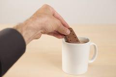 Tremper un biscuit de chocolat dans le thé Photos libres de droits