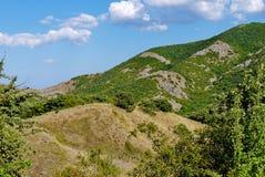 Trempez haut la pente couverte d'herbe sur le fond de ciel bleu photo libre de droits