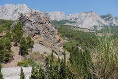 Trempez les falaises grandes sur le fond d'un ciel bleu entouré par la forêt dense images stock