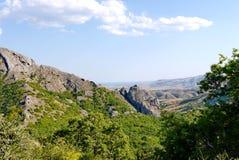 Trempez les pentes herbeuses sur le fond de hautes montagnes sans fin couvertes d'arbres photo stock