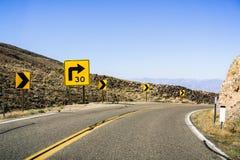 Trempez tourne-à-droite sur une route d'enroulement ; le signe signalé montrant 30 M/H a recommandé la vitesse ; La Californie image libre de droits
