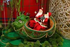 Trenó dois Santa Claus Riding Green Reindeer Shaped, uma decoração original da casa do Natal foto de stock