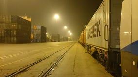 Tren con los carros en puerto en la noche Foto de archivo