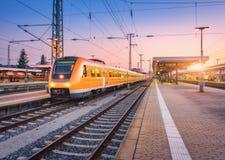 Tren de alta velocidad del pasajero en el ferrocarril en la puesta del sol Foto de archivo libre de regalías