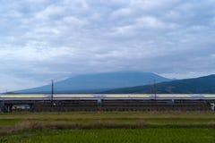 Tren de bala rápido que conduce y que pasa la montaña Fuji cerca de Tokio r fotografía de archivo libre de regalías