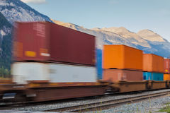 Tren de carga con los contenedores para mercancías que pasan las montañas Fotos de archivo