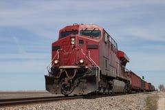 Tren de carga principal locomotor rojo grande en pradera foto de archivo