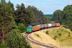 Tren de carga que pasa el bosque Imagen de archivo