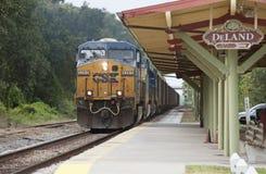 Tren de carga que pasa a través de una estación Imágenes de archivo libres de regalías