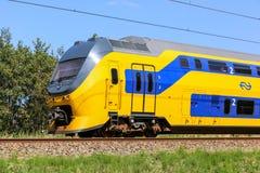 Tren de cercanías amarillo y azul holandés Imagenes de archivo