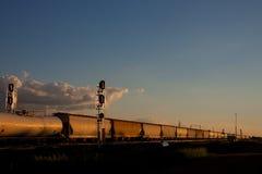 Tren de la puesta del sol que pasa torres de la señal fotografía de archivo