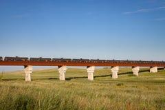 Tren de los coches del tanque negros que cruzan a Rusty Bridge fotos de archivo libres de regalías