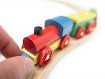Tren de madera colorido del juguete con la mano aislada en blanco fotos de archivo libres de regalías
