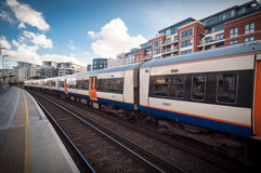 Tren de Overground que pasa cerca, en la estación imperial del muelle Foto de archivo libre de regalías