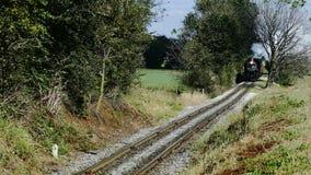 Tren de pasajeros del vapor que sopla a lo largo de las tierras de cultivo y del campo de Amish almacen de video