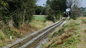 Tren de pasajeros del vapor que sopla a lo largo de las tierras de cultivo y del campo de Amish almacen de metraje de vídeo
