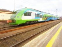 Tren de pasajeros moderno en el camino El trabajador examina la línea ferroviaria Tren de alta velocidad con la falta de definici fotografía de archivo