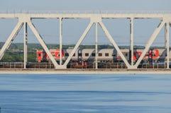 Tren de pasajeros que pasa el puente sobre el río en verano Fotografía de archivo libre de regalías