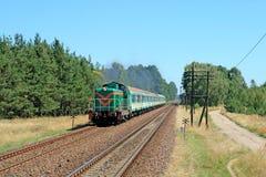 Tren de pasajeros que pasa a través de campo Imágenes de archivo libres de regalías