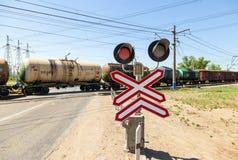 Tren del cargo que monta sobre un cruce ferroviario Imágenes de archivo libres de regalías