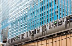 Tren del EL en Chicago debajo de la torre de cristal azul Fotografía de archivo libre de regalías