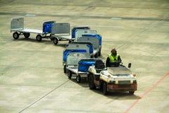 Tren del portador del equipaje del aeropuerto en la pista de despeque Imagen de archivo libre de regalías