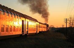 Tren del vapor durante puesta del sol Foto de archivo libre de regalías