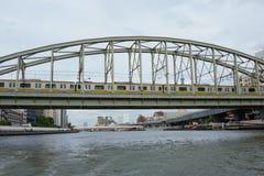 Tren eléctrico en el puente sobre el río de Tokio Sumida fotografía de archivo