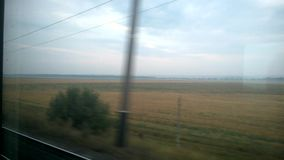 Tren, ferrocarril, ventana del tren, campo amarillo, árboles verdes, cielo azul almacen de metraje de vídeo