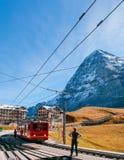 Tren ferroviario de Jungfrau en la estación de Kleine Scheidegg con el pico de Eiger y de Monch foto de archivo