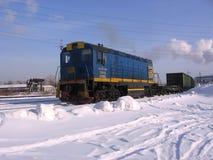 Tren locomotor de la carga en los carriles del ferrocarril industrial en el invierno foto de archivo