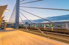Tren que acelera en una estación en la puesta del sol Imagen de archivo