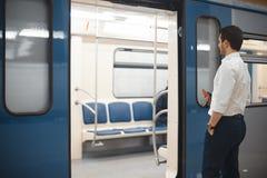 Tren que entra atractivo joven del hombre de negocios o del encargado en metro o subterráneo imagen de archivo libre de regalías