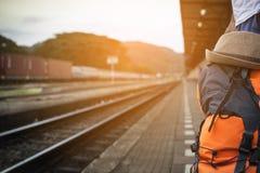 Tren que espera de la mochila del hombre en la estación de tren en Tailandia imagenes de archivo