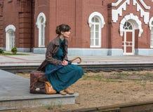 Tren que espera de la mujer joven para en la estación foto de archivo libre de regalías