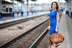 Tren que espera de la señora en el ferrocarril Fotografía de archivo libre de regalías