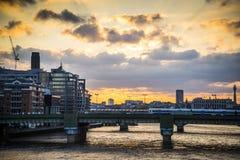 Tren que pasa sobre el puente ferroviario en la puesta del sol, Londres, Reino Unido de calle del cañón imágenes de archivo libres de regalías