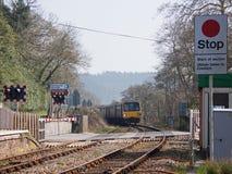 Tren que se acerca a un paso a nivel en Devon Reino Unido Foto de archivo libre de regalías