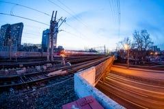 Tren que se mueve a lo largo de la plataforma en crepúsculo Imagen de archivo