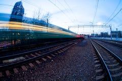 Tren que se mueve a lo largo de la plataforma en crepúsculo Fotos de archivo