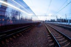 Tren que se mueve a lo largo de la plataforma en crepúsculo Imagen de archivo libre de regalías