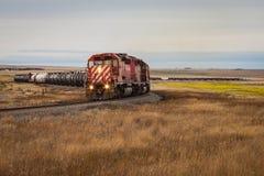 Tren rojo que zigzaguea a través de paisaje de la pradera fotografía de archivo libre de regalías