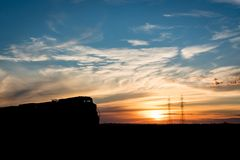Tren silueteado en la puesta del sol en la pradera canadiense fotos de archivo