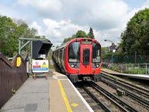 Tren subterráneo de Londres de la acción S8 que deja la estación de Chorleywood en la línea metropolitana ferrocarril imagen de archivo libre de regalías