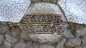 Trencadis mosaic in Parc Guell with ancient greek ornament. Trencadis is a type of mosaic used in Catalan modernism, created from broken tile shards. The Stock Photo