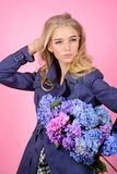 Trench coat fashion trend. Fashionable coat. Must have concept. Clothes and accessory. Woman blonde hair posing coat. With flowers bouquet. Girl fashion model stock photo