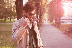 Trench coat. Handsome man wearing trench coat in park stock photography