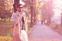 Trench coat. Handsome man wearing trench coat in park Stock Photos