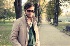 Trench coat. Handsome man wearing trench coat in park stock images